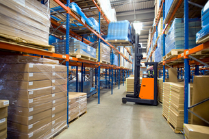 Warehouse worker moving boxes on pallet with forkliftの写真素材 [FYI02114102]