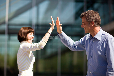Happy young woman and mature man giving the 'high-five' gestureの写真素材 [FYI02114107]