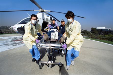 Doctors and paramedics rushing patient on gurney from emergency airlift helicopterの写真素材 [FYI02114117]