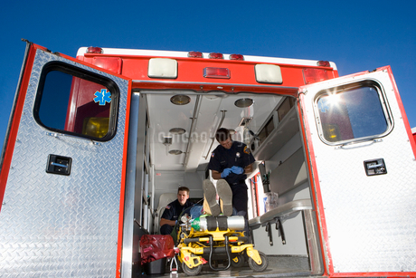 Paramedics with man on stretcher in ambulance, low angle viewの写真素材 [FYI02114124]