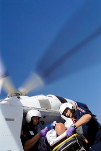 Paramedics removing patient on gurney from emergency airlift helicopterの写真素材 [FYI02114125]