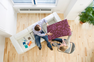 Couple looking at wallpaper sample in living roomの写真素材 [FYI02114161]