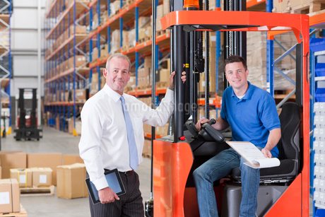 Portrait of smiling supervisor and worker in forklift in distribution warehouseの写真素材 [FYI02114186]