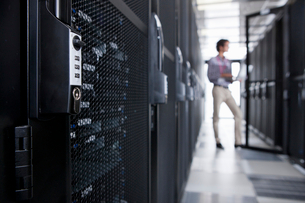Technician with laptop, checking aisle of server storage cabinets in data centerの写真素材 [FYI02114194]