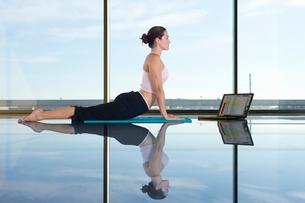 Woman doing yoga next to laptopの写真素材 [FYI02114253]