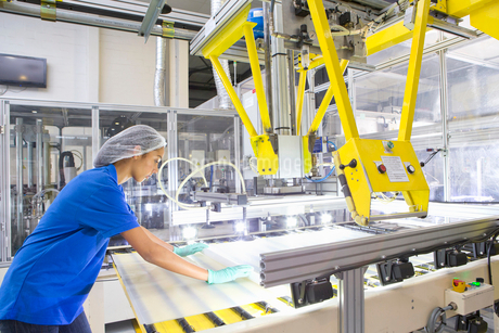 Factory floor worker coating glass for solar panel assembly on production lineの写真素材 [FYI02114288]