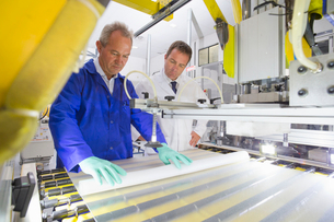 Engineer checking worker coating solar panel glass on production line on factory floorの写真素材 [FYI02114322]