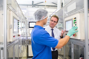 Businessman owner discussing automated manufacturing process with worker on factory floor productionの写真素材 [FYI02114324]