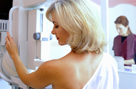 Woman with bare chest undergoing mammogram with radiologist in backgroundの写真素材 [FYI02114325]