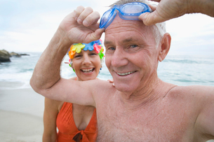 Mature woman in swimming costume and cap smiling by man with goggles, portraitの写真素材 [FYI02114359]