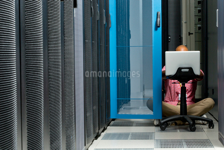 Technician with laptop checking server in data centreの写真素材 [FYI02114365]