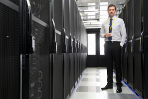 Manager standing in aisle of storage cabinets in data centerの写真素材 [FYI02114411]