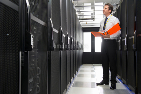 Manager with folder, checking aisle of storage cabinets in data centerの写真素材 [FYI02114419]