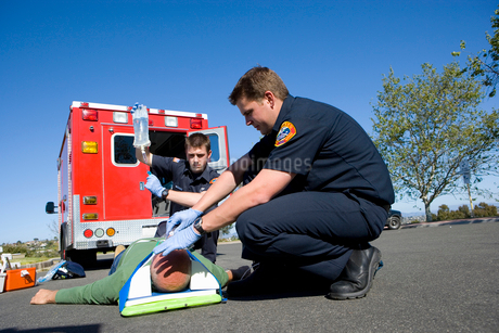 Paramedic and colleague helping man on stretcher, low angle viewの写真素材 [FYI02114442]