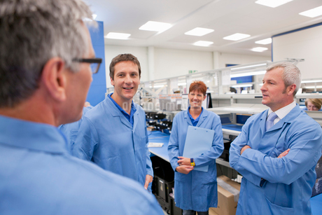 Technicians in lab coats talking in hi-tech manufacturing plantの写真素材 [FYI02114533]