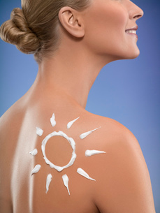 Close-up of young woman with sunscreen in shape of sun on back shoulder, studio shotの写真素材 [FYI02114566]