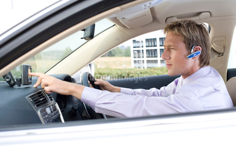 Businessman with bluetooth headset setting gps device in carの写真素材 [FYI02114572]