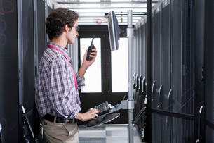 Technician, on walkie talkie, working on computer in aisle of server storage cabinetsの写真素材 [FYI02114622]