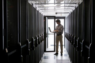 Technician with laptop, checking aisle of server storage cabinets in data centerの写真素材 [FYI02114637]