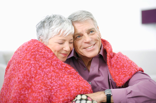 Portrait of affectionate couple cuddling under blanketの写真素材 [FYI02114669]
