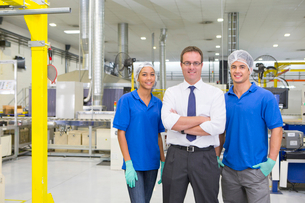Businessman and technicians smiling at camera in solar panel factory production lineの写真素材 [FYI02114707]