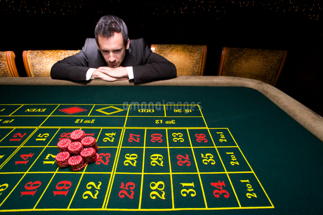 Businessman looking at pile of gambling chips on roulette tableの写真素材 [FYI02114870]