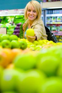 Woman choosing apples in grocery storeの写真素材 [FYI02114874]