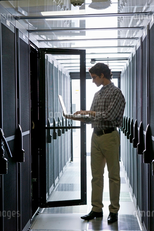 Technician with laptop, checking aisle of server storage cabinets in data centerの写真素材 [FYI02114906]