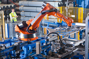 Worker controlling robotic machinery lifting steel fencing on production line in manufacturing plantの写真素材 [FYI02114919]