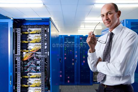 Portrait of confident businessman in network server roomの写真素材 [FYI02114949]
