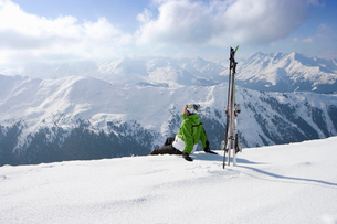 Man sitting in snow on mountain top with skisの写真素材 [FYI02114961]