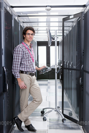 Technician, looking at camera, working on computer in aisle of server storage cabinetsの写真素材 [FYI02115010]