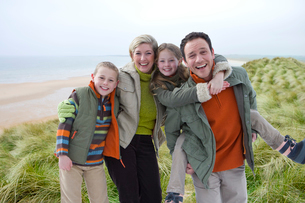 Portrait of smiling family in warm clothing on beachの写真素材 [FYI02115114]