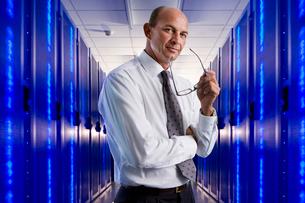 Portrait of businessman in network server roomの写真素材 [FYI02115161]