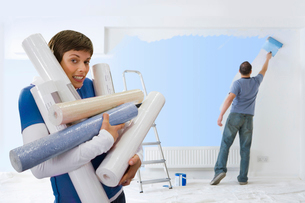 Woman carrying armful of wallpaper while husband paintsの写真素材 [FYI02115185]