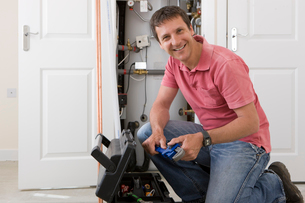 Portrait of smiling handyman with wrench kneeling before toolbox in front of boiler in closetの写真素材 [FYI02115195]
