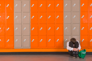 Unhappy student sitting on floor near school lockersの写真素材 [FYI02115223]