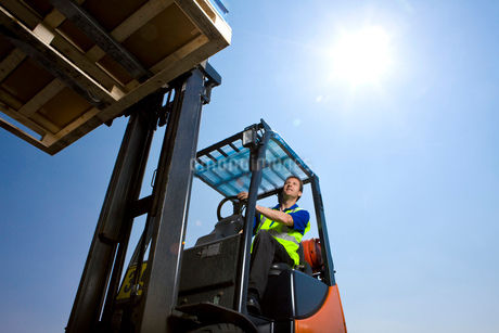 Worker driving forklift moving inventoryの写真素材 [FYI02115265]