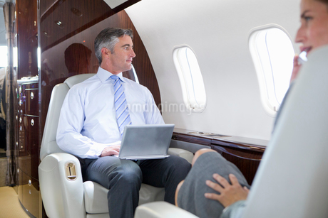 Businesswoman on phone and Businessman with digital tablet having meeting on private jetの写真素材 [FYI02115335]