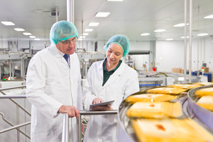 Quality control workers with digital tablet at production line in cheese processing plantの写真素材 [FYI02115391]