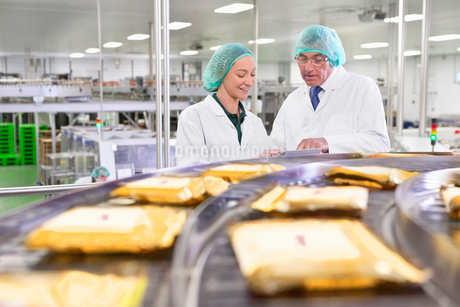 Quality control workers with digital tablet at production line in cheese processing plantの写真素材 [FYI02115392]