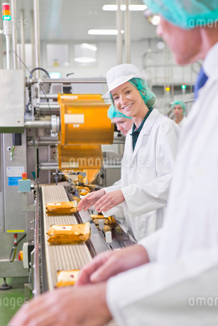 Portrait smiling worker at production line in cheese processing plantの写真素材 [FYI02115394]