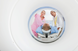 Doctor and technician nurse preparing patient at CT scanner tube in hospitalの写真素材 [FYI02115408]