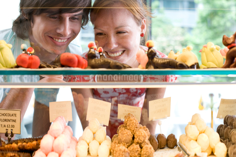 Couple looking at food on display in bakery, view through glassの写真素材 [FYI02115427]