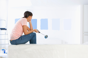 Woman sitting on sofa and examining blue paint samples on living room wallの写真素材 [FYI02115429]