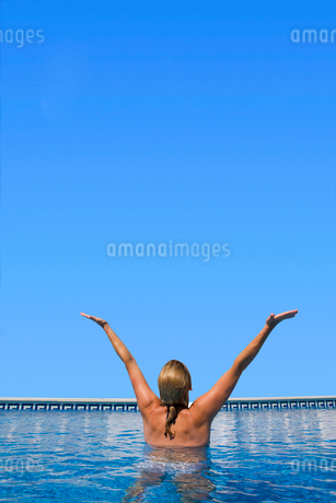 Woman standing with arms raised in swimming poolの写真素材 [FYI02115431]