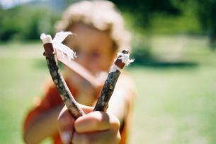 Close up of boy aiming homemade slingshotの写真素材 [FYI02115451]