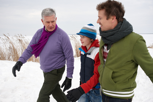 Grandfather, son, and boy walking together on winter dayの写真素材 [FYI02115471]