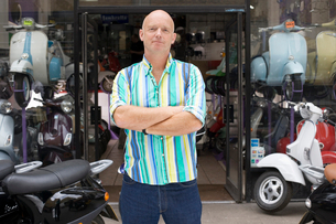 Mature man standing in front of scooter shop, arms folded, front view, portraitの写真素材 [FYI02115477]