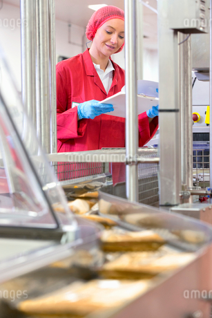 Worker with clipboard at production line in cheese processing plantの写真素材 [FYI02115479]